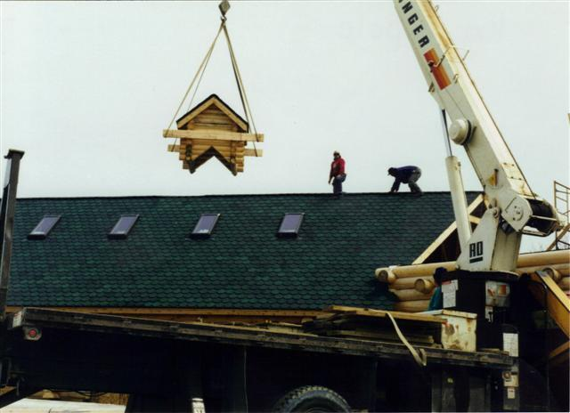 log cupola hoisted by crane